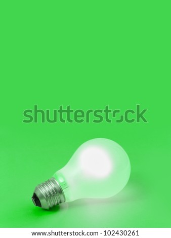 Lighting lamp on green - abstract technology background - stock photo