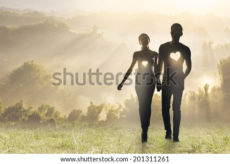 Lighting love, Silhouette of Asian couple hold hands walking on grassland. - stock photo