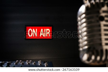 lighting of on air signboard in sound studio and retro  microphone is foreground - stock photo