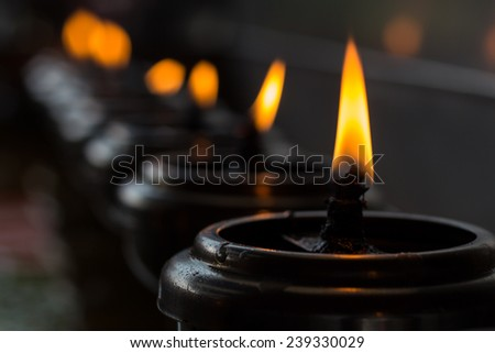 Lighting of Praying candles in a temple - stock photo