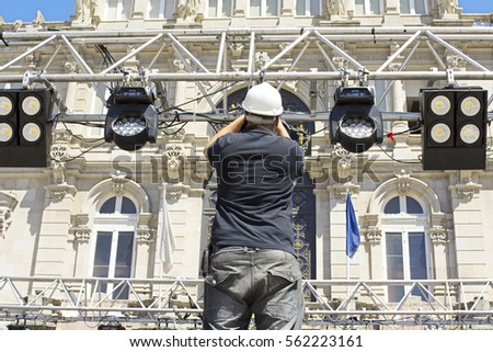lighting technician installing professional lighting equipment for concert stage  installation with led lights and projectors & Professional Lighting Equipment Concert Stage Installation Stock ... azcodes.com