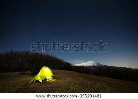 lighting tent and Etna Volcano under moonlight and starry sky , Nebrodi Park in Sicily   - stock photo