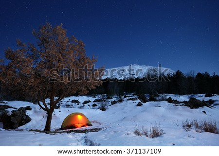 lighting tent and oak tree in the snow of Etna Park under starry sky, Sicily  - stock photo