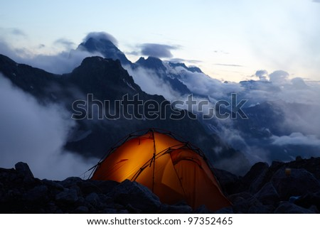 Lighting tent at evening in mountains - stock photo