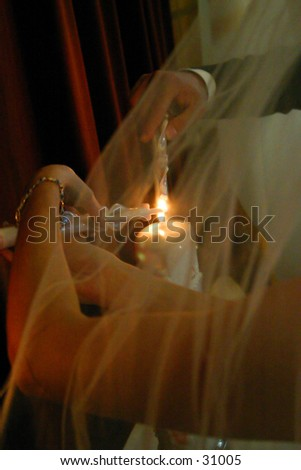 Lighting the unity candle at a wedding through the veil.