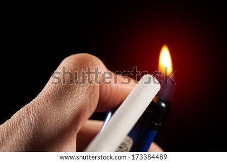 lighting up a cigarette, red glowing background