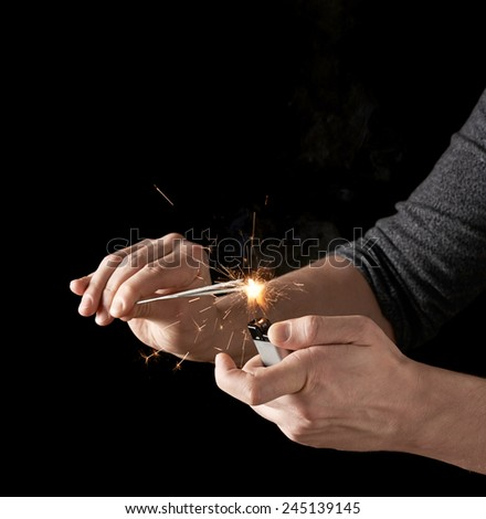 Lighting up a sparkler with lighter, low-key composition isolated over the black background - stock photo