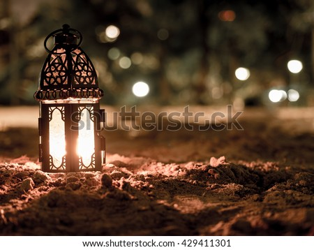 lighting with candle inside Lantern shining on sand floor playground, children play with it in Ramadan night, also known and called as Ramadan Kareem Lantern - stock photo