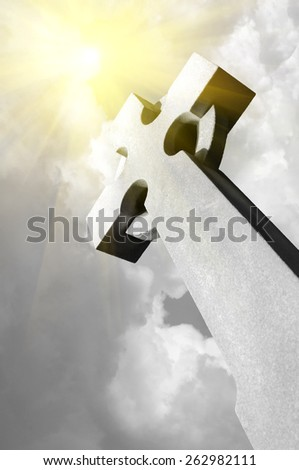 lighting with clouds breaking the sunshine over stone cross - stock photo