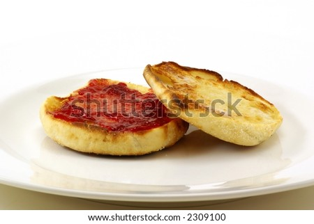 Lightly toasted sourdough english muffins with butter and strawberry preserves on white background. - stock photo