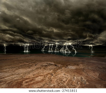 Lightning and ominous clouds over a desert plain and distant lake - stock photo