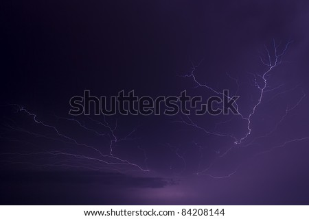 Lightning arcs across the sky illuminating clouds with a purplish flash. Great detail in the branching and forking of the lightning bolts. Photographed in central Indiana in the Midwest of the USA. - stock photo