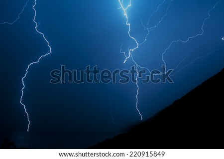 Lightning behind the hill and over the sea.