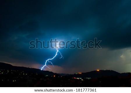 Lightning bolt from cloud to ground lightning on ridge - stock photo