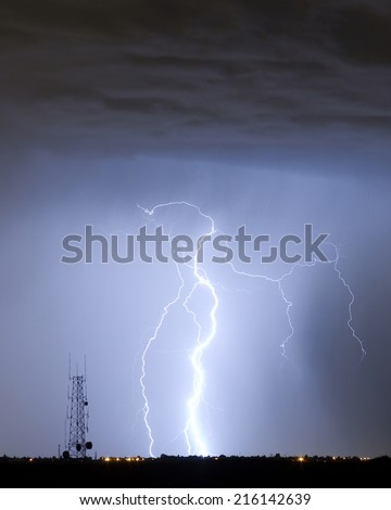 Lightning bolt striking next to a communication tower  in Colorado.  - stock photo