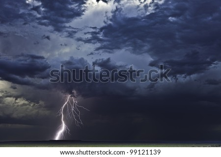 Lightning from a super-cell thunderstorm in Tornado Alley strikes down to the ground. - stock photo
