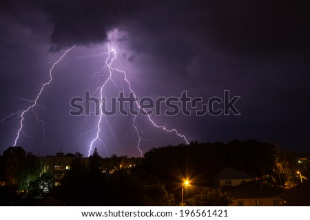 Lightning in night sky over small town - stock photo
