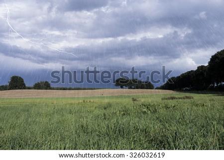 Lightning in rainy landscape - stock photo
