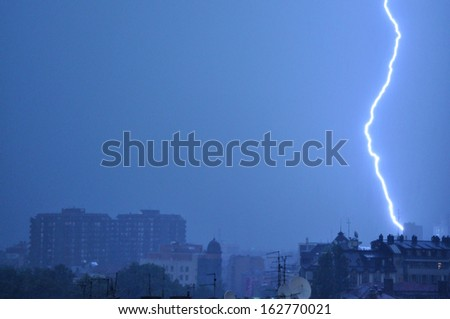 lightning in the blue sky above the city