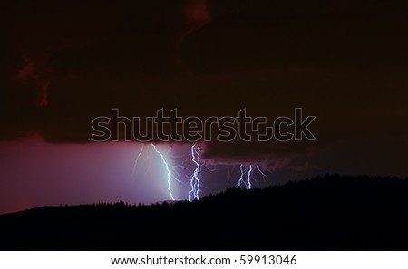 Lightning over forest - stock photo