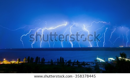 Lightning over night river in the blue sky