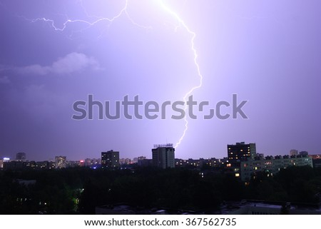 lightning over the city cuts the sky into two parts