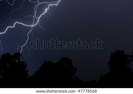 Lightning over the trees - stock photo