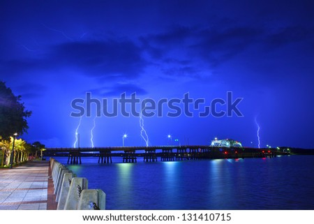 lightning over waterfront and bridge at night - stock photo