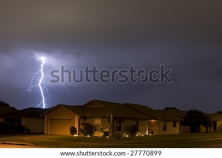 Lightning strike at night very near homes - stock photo