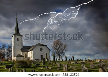 Lightning strike from a darkening cloud near a graveyard and church. - stock photo