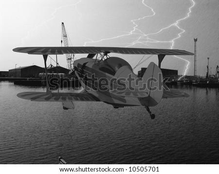 Lightning strike in a dockyard with a biplane flying - stock photo