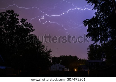 Lightning strike in the clouds above. - stock photo