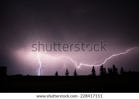 Lightning strike in the middle of a field at night - stock photo