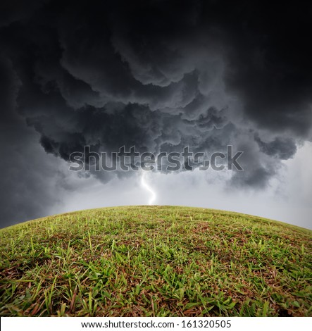 Lightning strike on a green grassy hilltop during a dramatic thunderstorm.   - stock photo