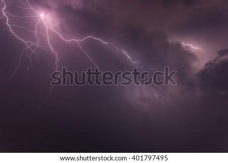 Lightning strike on the dark cloudy sky - stock photo