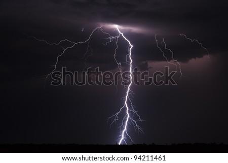 Lightning strike over a field - stock photo