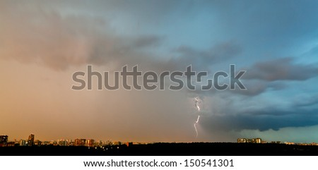 lightning strike over city in summer evening