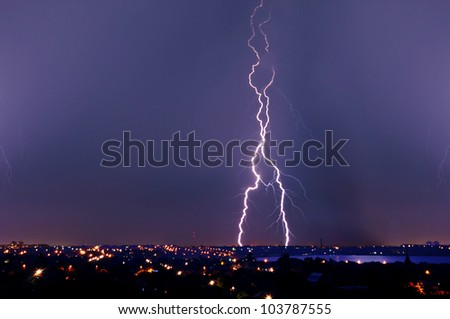 Lightning strike over dark blue sky in night city - stock photo