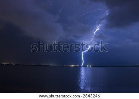 Lightning strike over lake - stock photo