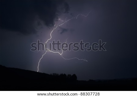 Lightning strike within a thunderstorm at night