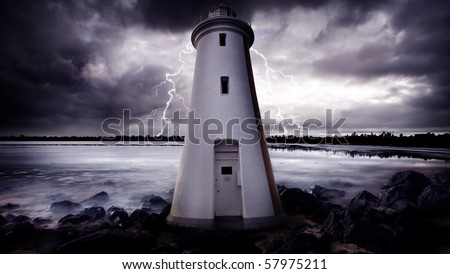 Lightning Strikes behind a lighthouse - stock photo