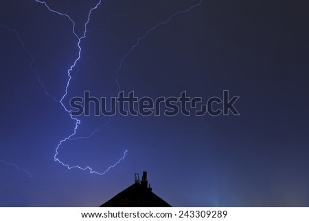 Lightning strikes down from the sky at night - stock photo