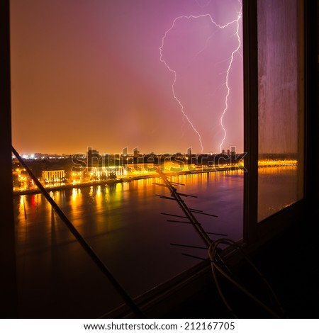 Lightning strikes in the city seen through the window, thunder in the night - stock photo