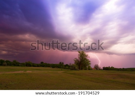 Lightning strikes in the field. - stock photo