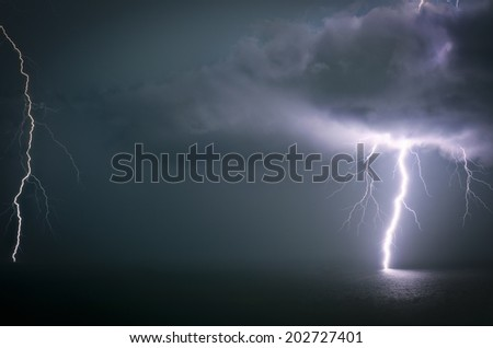Lightning strikes the sea through a cloud during a large thunderstorm in Durban, South Africa - stock photo