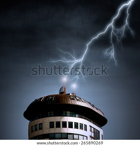 Lightning strikes top of appartment building antenna - stock photo