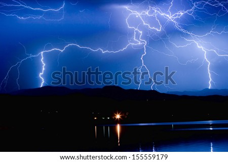Lightning striking over McIntosh Lake in Longmont Colorado, Boulder County, hitting the foothills of the Front Range of the Rocky Mountains.  - stock photo