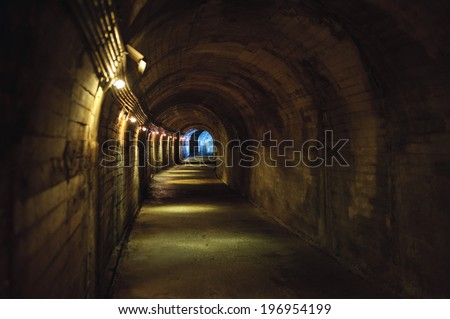 Lights along a dark tunnel with an arched ceiling. - stock photo