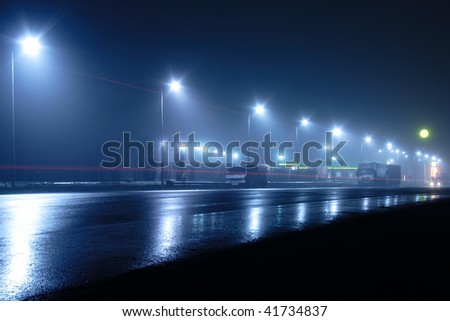 lights and light traces on road at night and in the fog - stock photo