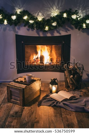 Lights decorated fireplace, lantern, coffee, sweets and a book. Winter christmas relaxing home holiday concept.